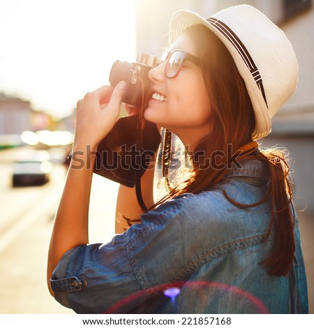 Outdoor summer fashion sensual portrait of pretty young beautiful brunette woman hipster photographer tourist taking pictures in old city in summer evening and smiling  - stock photo