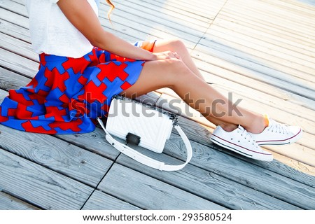 Outdoor summer lifestyle fashion portrait of young hipster stylish woman walking,sitting on the wooden floor,wearing vintage clothes,stylish clothes,clear fresh colors.bright colors,trendy outfit,bag - stock photo