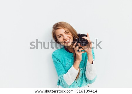 Outdoor summer lifestyle image of young pretty hipster woman having fun, make pictures on professional camera, city center Europe, cute white vintage outfit and sunglasses, fun ,joy, emotions. - stock photo