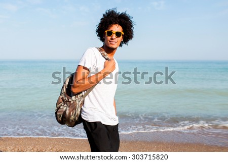 Outdoor summer lifestyle portrait of stylish young  man with backpack wearing sunglasses walking  on sunny tropical beach.   - stock photo