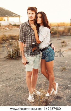Outdoor summer portrait of fashion casual couple posing outdoor in abandoned place in sunset and having fun - stock photo