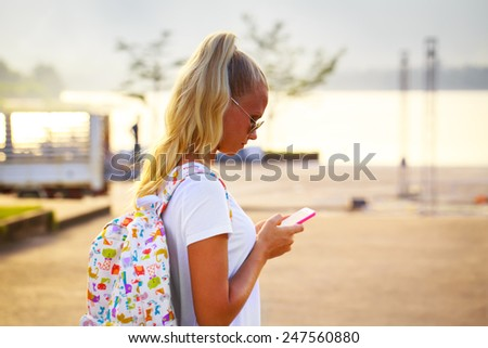 Outdoor summer portrait of gorgeous young blonde woman looking at her smartphone - stock photo