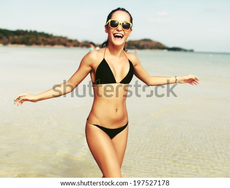 Outdoor summer portrait of pretty sport style woman in black bikini running on the beach on tropic island close to the sea and smiling having fun - stock photo