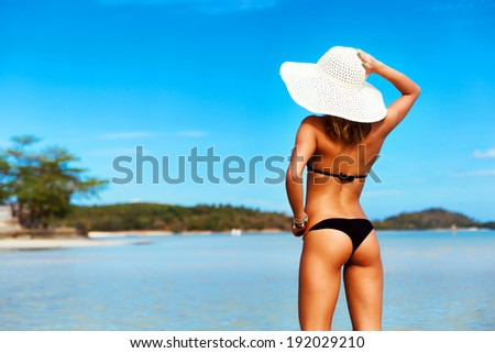 Outdoor summer portrait of pretty young tanned sexy hot woman standing back in bikini and sun hat on the beach and blue water and having fun on vacation - stock photo