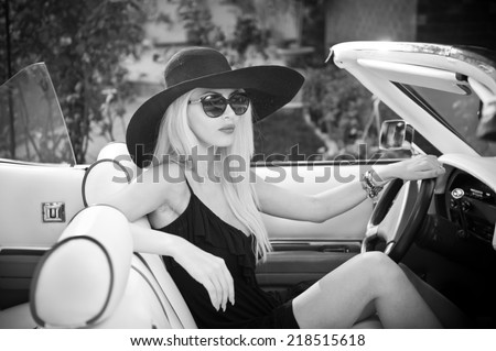Outdoor summer portrait of stylish blonde vintage woman driving a convertible retro car. Fashionable attractive fair hair female with black hat in withe leather vehicle. Black and white outdoors shot. - stock photo