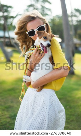 Outdoor summer portrait of stylish hipster girl holding a dog at the park,smiling and having fun during their vacation,wear summer sunglasses,summer bright clothes,yellow summer shirt and white skirt - stock photo