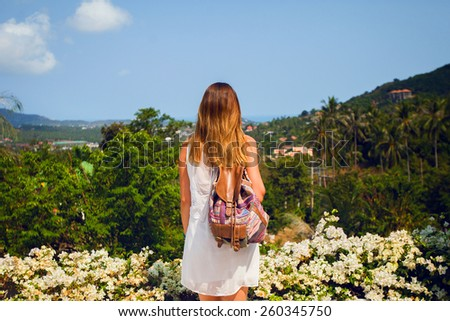 Outdoor summer portrait of young attractive  woman looking to the  tropical  mountains  , enjoy  fresh air and wonderful view , wearing stylish  whit dress and colorful backpack . - stock photo