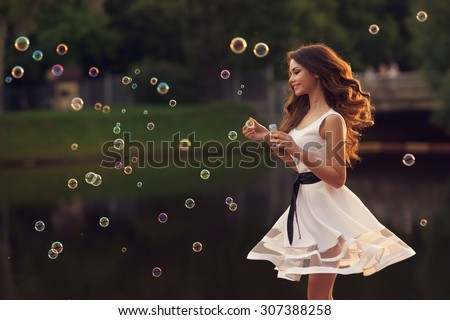 Outdoor summer portrait of young beautiful happy woman making soap bubbles in park or at nature. Joyous happy girl in white dress - stock photo