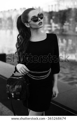 Outdoor summer portrait of young beautiful pretty classy stylish trendy girl in black dress with small red handbag - stock photo