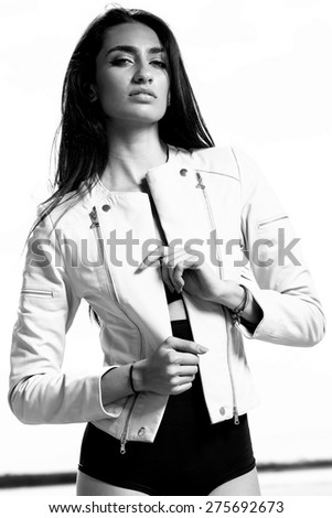 Outdoor summer portrait of young pretty cute brunette girl. Beautiful woman posing in desert with leather jacket. Young woman outdoors portrait