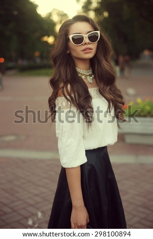 Outdoor summer portrait of young stylish classy woman with long curly brown hair. Elegant girl posing in white blouse, black skirt,sunglasses and necklace in city park at sunset. Soft light full body - stock photo