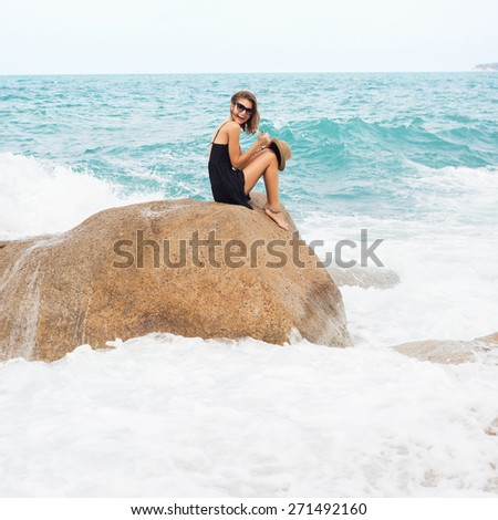 Outdoor summer sunny fashion portrait of pretty young sensual woman posing in black dress on the rocks and have fun alone on the ocean seashore. Outdoors lifestyle portrait - stock photo