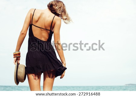 Outdoor summer sunny fashion portrait of pretty young sensual woman posing in black dress on the rocks on the ocean seashore. Outdoors lifestyle portrait - stock photo