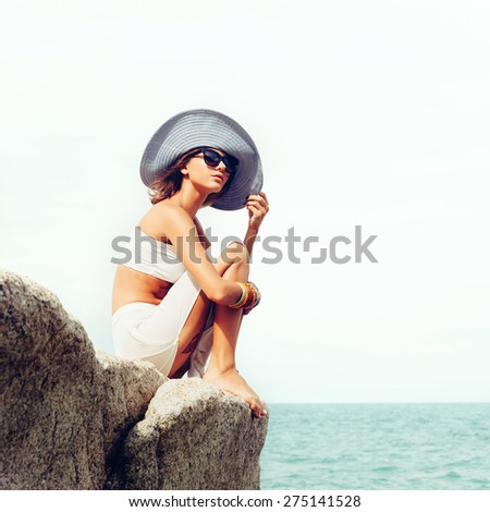 Outdoor summer sunny fashion portrait of pretty young sensual woman posing in hat and white dress on the rocks and have fun alone on the ocean seashore. Outdoors lifestyle portrait - stock photo