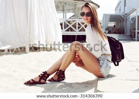 Outdoor summer vacation lifestyle portrait of pretty young brunette woman having fun on the beach