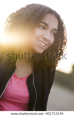 Outdoor sunset sunrise portrait with golden sunlight lens flare of beautiful happy mixed race African American girl teenager female young woman smiling with perfect teeth - stock photo