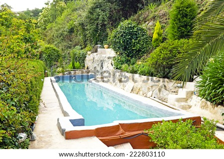 Outdoor swimming pool in nature - stock photo