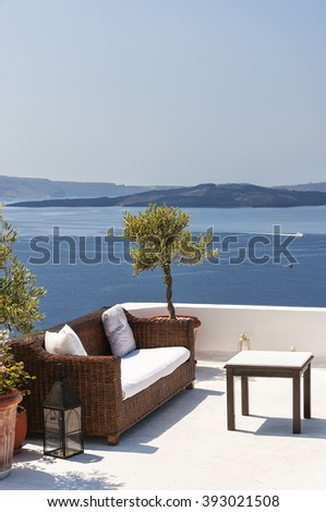 Outdoor table and sofas on terrace overlooking sea, Oia Village, Santorini, Cyclades, Greece. - stock photo
