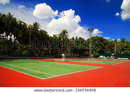 Outdoor tennis hard courts against blue sky - stock photo