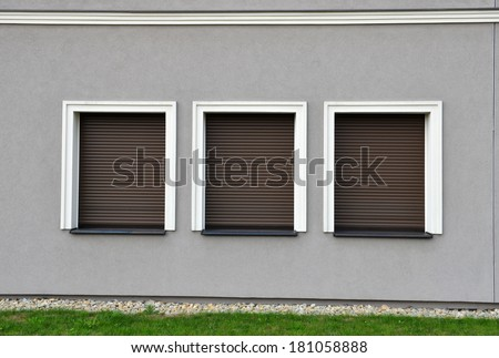 Outdoor three window blinds closed on grey wall - stock photo