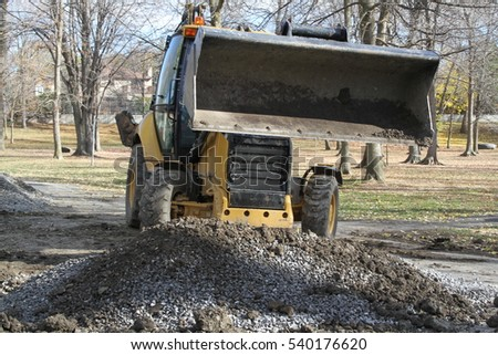 Outdoor tractor shovel collects gravel