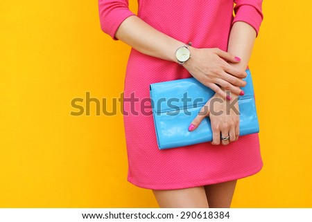 Outdoor trendy girl near yellow street wall .Stylish pink dress and blue clutch. - stock photo