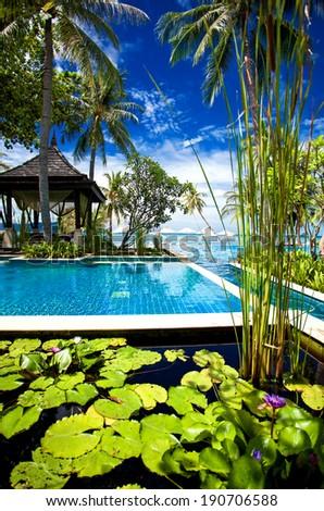 Outdoor tropical massage gazebo on the beach next to swimming pool - stock photo