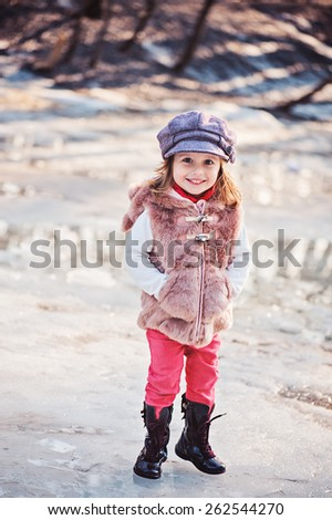 outdoor vertical portrait of happy toddler child girl in faux fur coat with melting snow on background