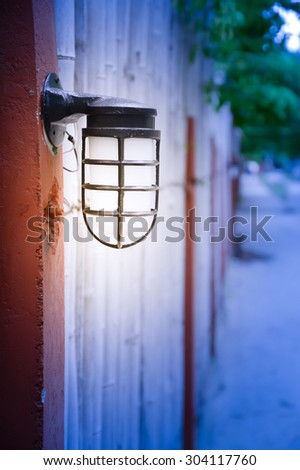 Outdoor Wall Lamp on bamboo fence in park - stock photo