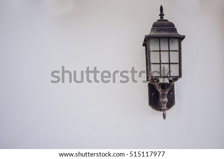 Outdoor wall lantern. Old beautiful lantern an white nice wall. Old iron street lantern on a white wall. Place for text.
