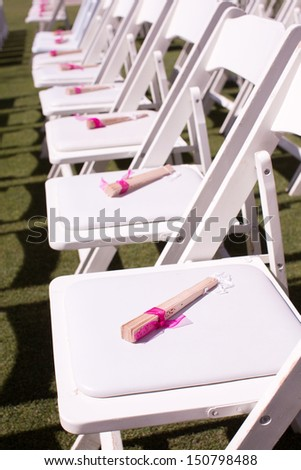 Outdoor Wedding Ceremony Chairs with Paper Fans - stock photo