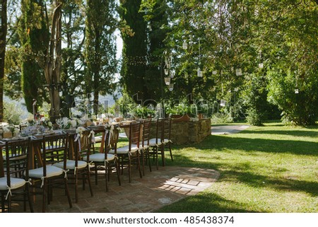 Outdoor wedding ceremony reception banquet hold in green park forest area decorated in rustic style, countryside decoration