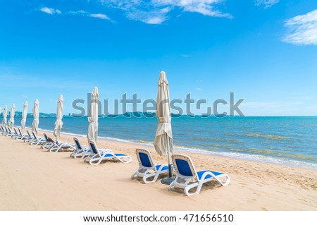 Outdoor with umbrella and chair on beautiful tropical beach and sea and blue sky background - boost up colour and lighting processing style