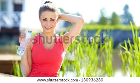 Outdoor workout woman. Fitness woman runner relaxing drinking water after training outside in  park - stock photo