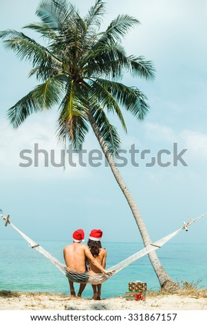 Outdoor  young couple sitting on a hammock under the palm trees celebrate new year on tropical hot countries with gifts and hugs,enjoy their holidays on hot countries,sea background,Phuket,Thailand