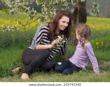 Outdoor young woman with her daughter - stock photo