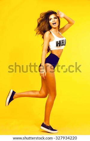 Outdoor young women  jumping at white wall. Lifestyle portrait of laughing woman with playful mood,jumping and having fun,listening favorite music at earphones,stylish vintage outfit,fresh colors.  - stock photo