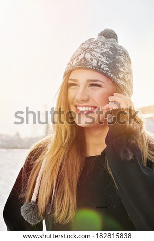 Outdoors closeup portrait of cute happy young blonde Caucasian teenage girl speaking on the phone laughing. - stock photo
