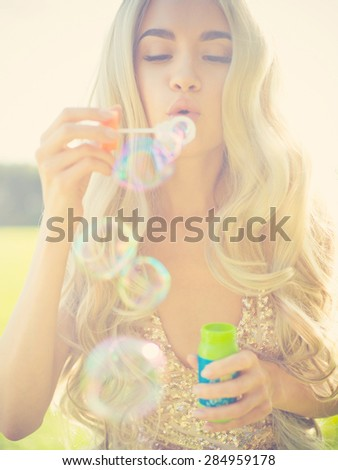 Outdoors fashion photo of beautiful blonde blowing bubbles  - stock photo