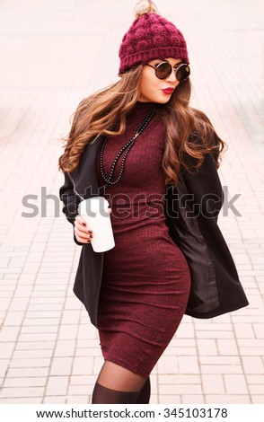 Outdoors fashion portrait of beautiful sexy brunette woman, posing on a city street. Drinking coffee. Perfect skin facial make-up. Wearing a fashionable coat, burgundy dress, hat and sunglasses  - stock photo