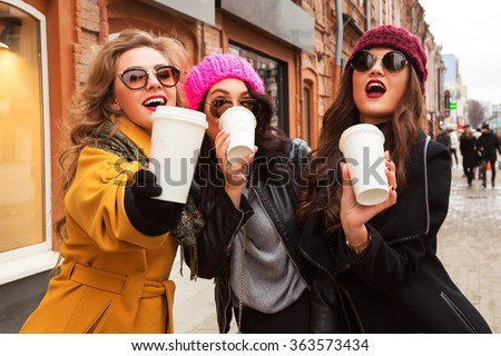 Outdoors fashion portrait of company cheerful pretty girls friends drinking coffee. Walking in the city. Talking and going shopping. Wearing stylish outerwear, sunglasses and hats. Bright make up - stock photo