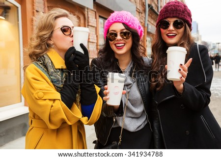 Outdoors fashion portrait of three young beautiful women friends drinking coffee. Smiling and going shopping. Kissing a cup of coffee. Wearing stylish outerwear, hats and sunglasses. Bright make up - stock photo