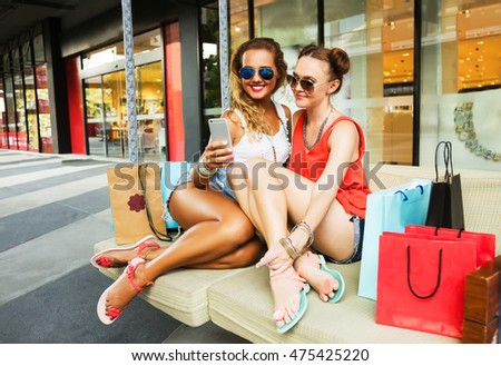 Outdoors fashion portrait of two young beautiful women friends in shopping mall with a lot of shopping bags. Making selfie. Smiling and happy after shopping. Wearing stylish t-shirts and sunglasses.