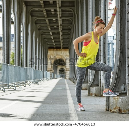 Outdoors fitness in Paris. Full length portrait of young woman jogger relaxing after workout on Pont de Bir-Hakeim bridge in Paris