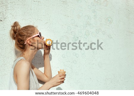 Outdoors lifestyle portrait of happy girl blowing soap bubbles