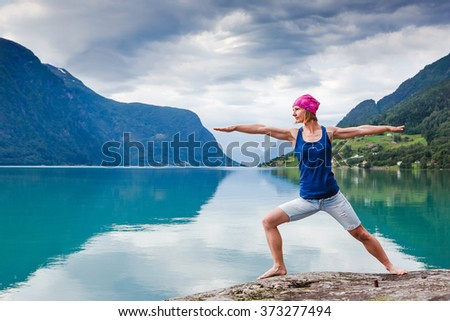 young woman practicing yoga between mountains stock photo