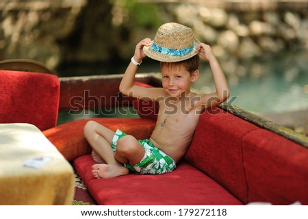 Outdoors on a red couch resting fun boy in a hat - stock photo