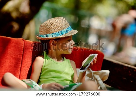 Outdoors on a red couch resting fun boy in a hat with phone