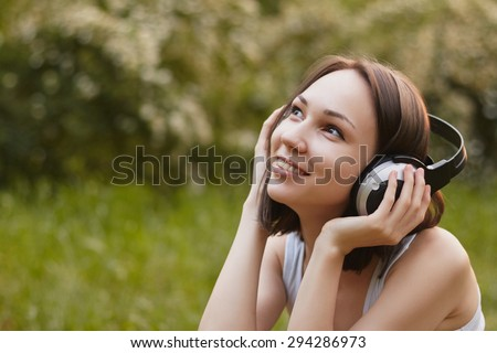 Outdoors photo of smiling girl listening music on green blur background