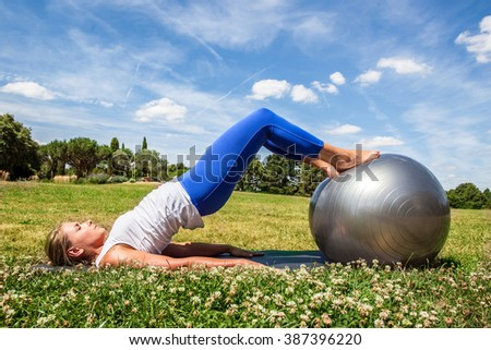 outdoors pilates exercise - young blond woman doing fitness, toning stomach with feet on sports ball in green grass, summer daylight - stock photo